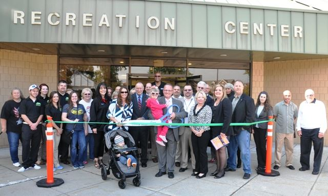 A group of people gathered in front of the Recreation Center for a ribbon-cutting ceremony.