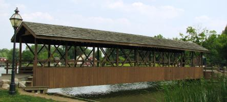 A covered bridge stretching over a stream.